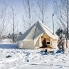 bell tent in snow with stove