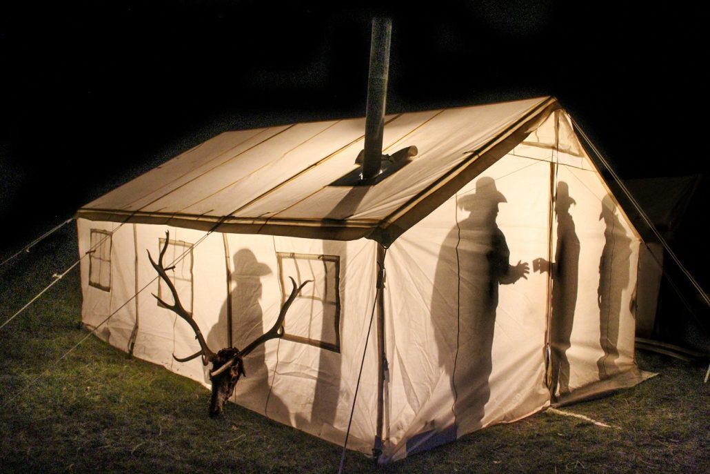 people talking in a canvas tent at night